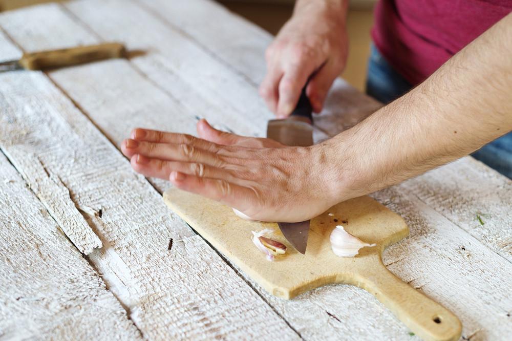 Unrecognizable man in the kitchen peeling garlic