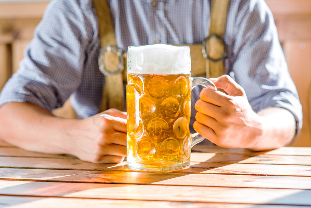 Unrecognizable man in traditional bavarian clothes sitting at the table, holding mug of beer. Oktoberfest.