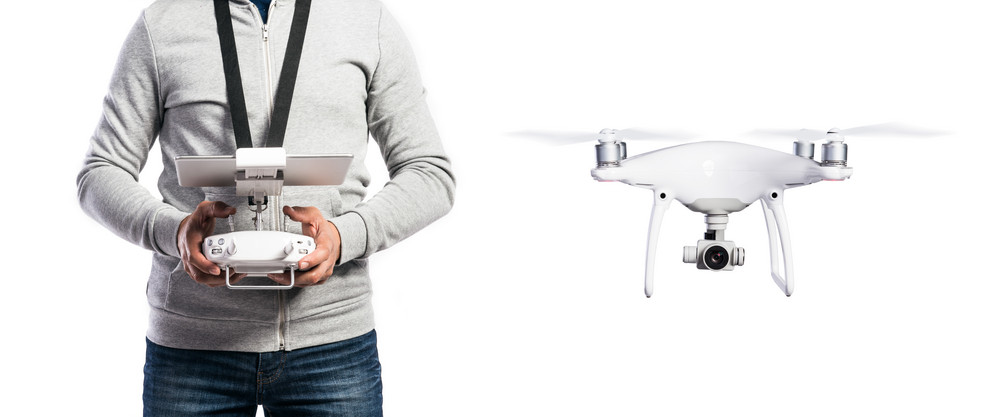 Unrecognizable man with remote control and flying drone with camera. Studio shot on white background, isolated.