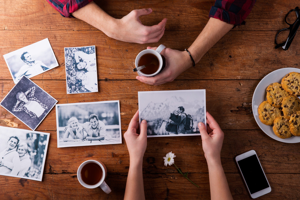 Unrecognizable mans and womans hand. Looking at their black and white photos. Couple in love. Cookies and tea, daisy flower, smart phone. Valentines day composition. Studio shot on brown wooden background.