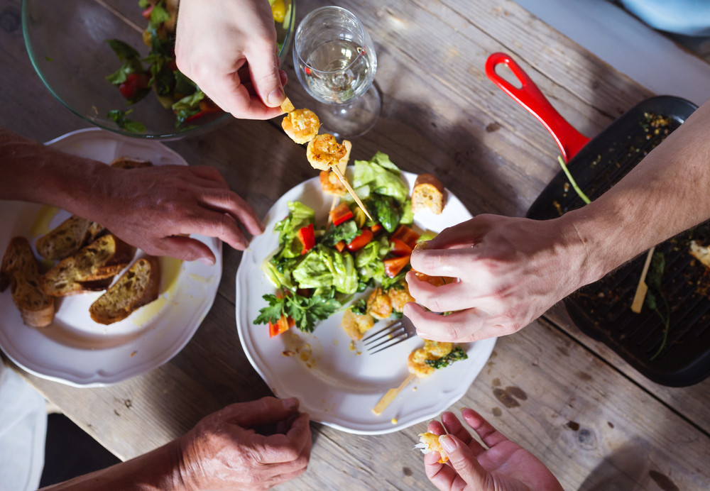 Unrecognizable people eating prawns, salad and bread together