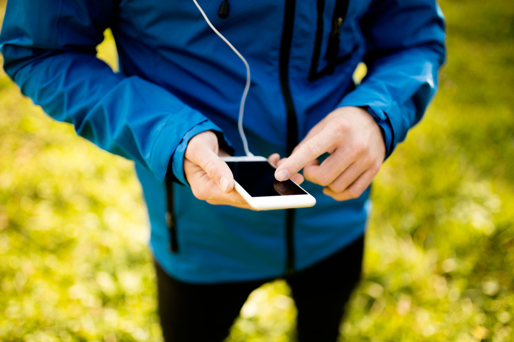 Unrecognizable runner outside in sunny autumn nature using a fitness app on his smartphone. Using phone app for tracking weight loss progress, running goal or summary of his run.