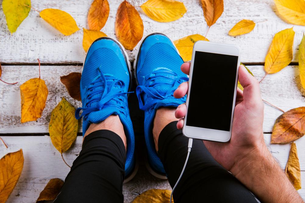 Unrecognizable runner with smart phone. Studio shot on wooden background.