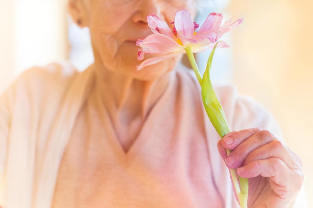 Unrecognizable senior woman holding a pink flower.