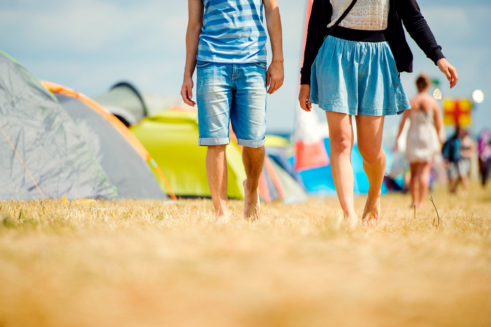 Unrecognizable teenage couple at tent music festival walking, sunny summer, close up of legs