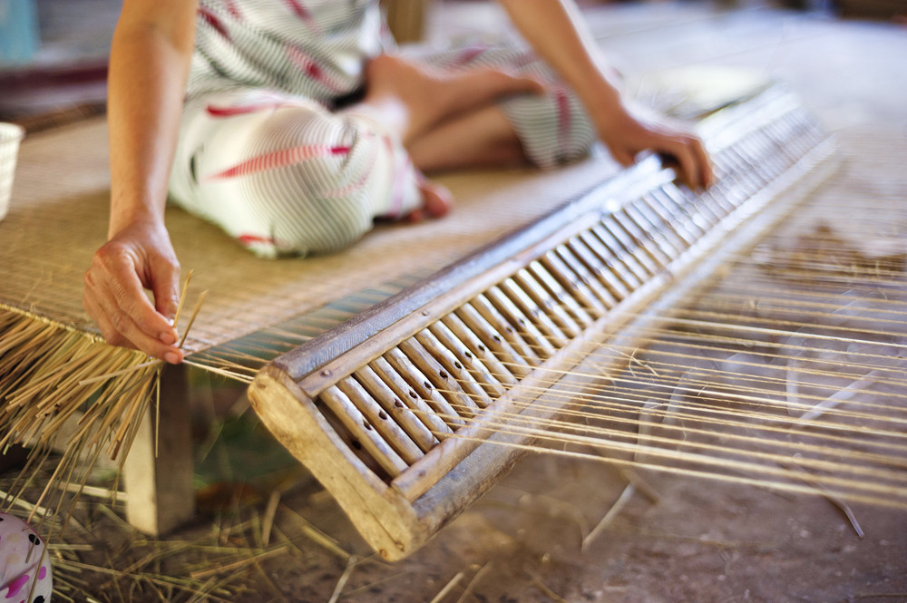 Unrecognizable vietnamese woman weaving a bamboo mat