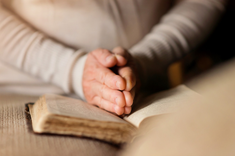 Unrecognizable woman holding a bible in her hands and praying