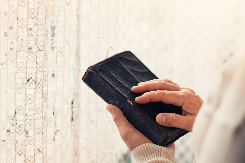 Unrecognizable woman holding a bible in her hands