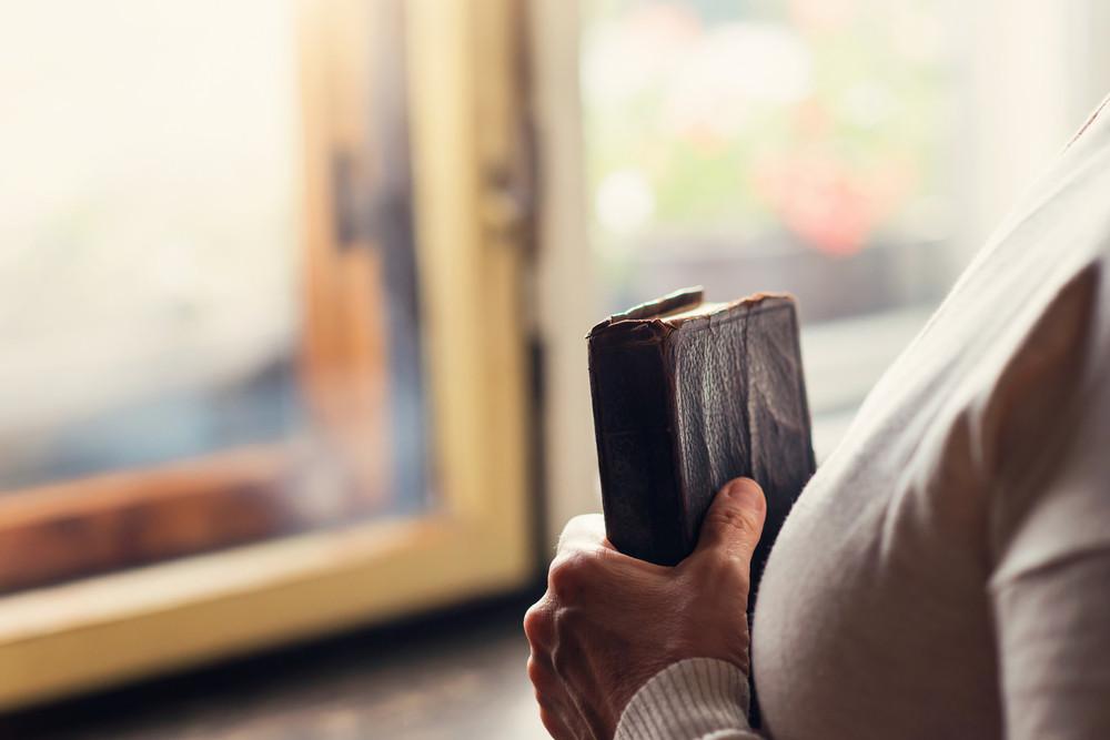 Mulher irreconhecível segurando uma bíblia nas mãos