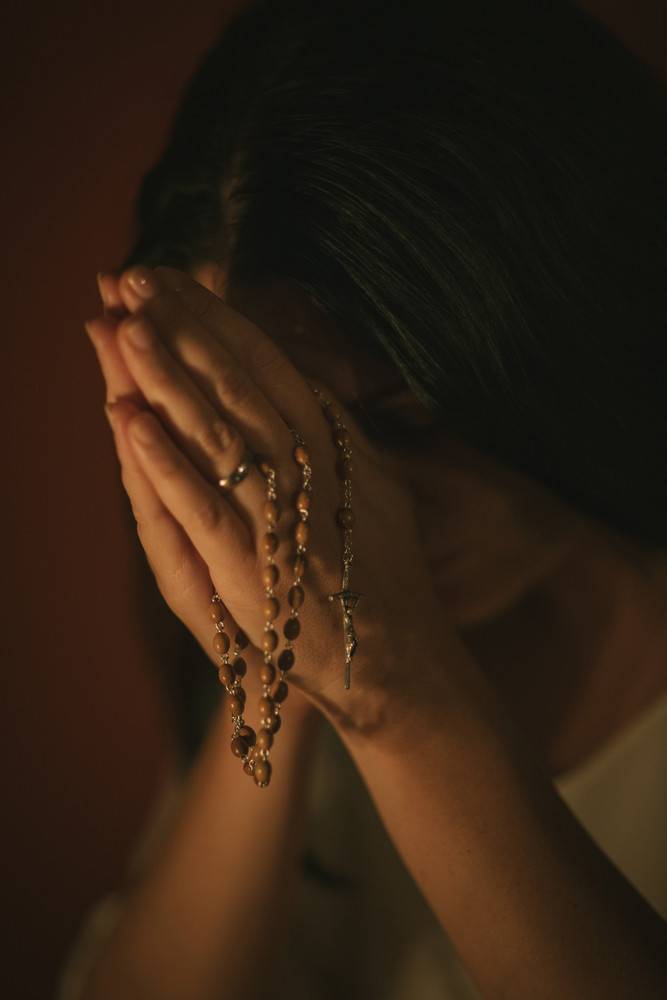 Unrecognizable woman with a rosary praying in the church