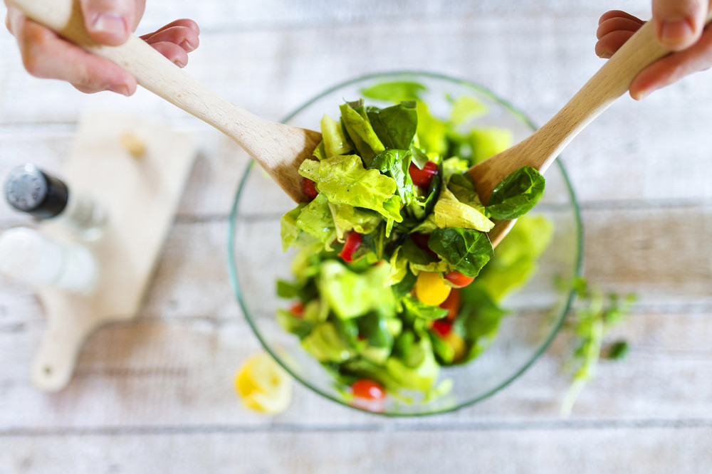 Unrecognizable young man in the kitchen preparing green salad