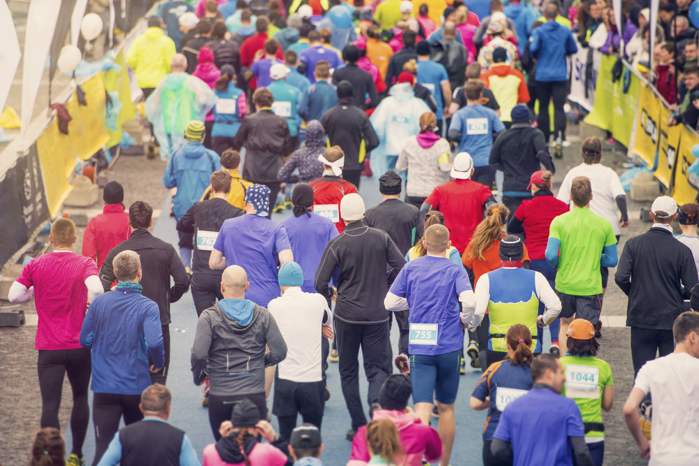 Unrecognizable young runners at the start of a city race