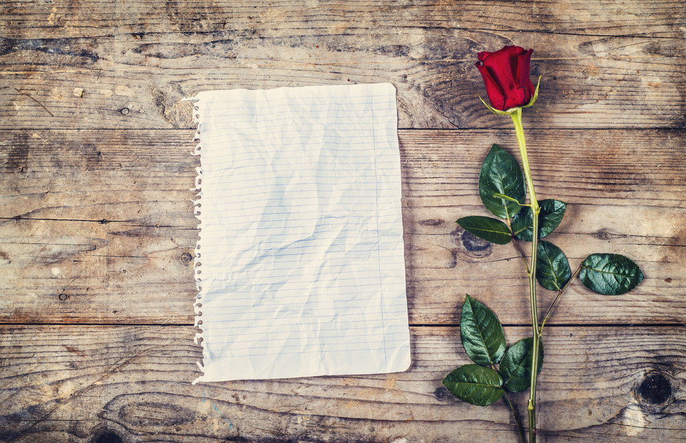 Valentine´s day composition of rumpled sheet of paper or blank love letter and red rose. Studio shot on a wooden floor background.