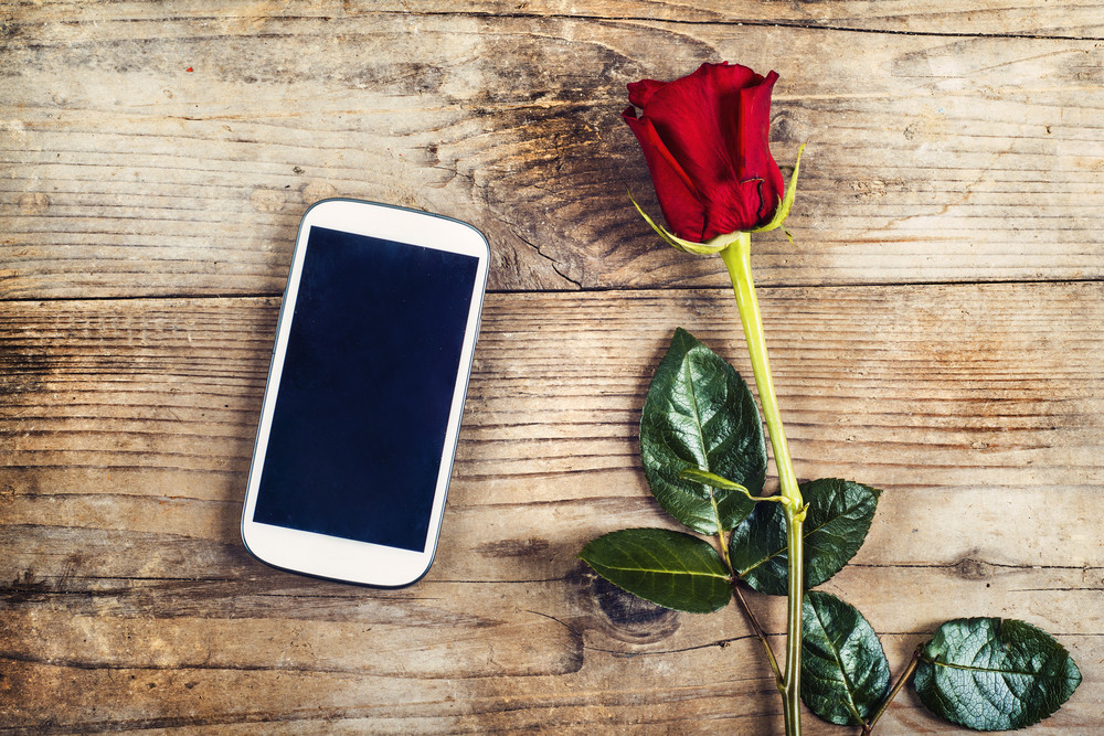 Valentine´s day composition of yet not written love message in a phone and a red rose. Studio shot on a wooden floor backround.