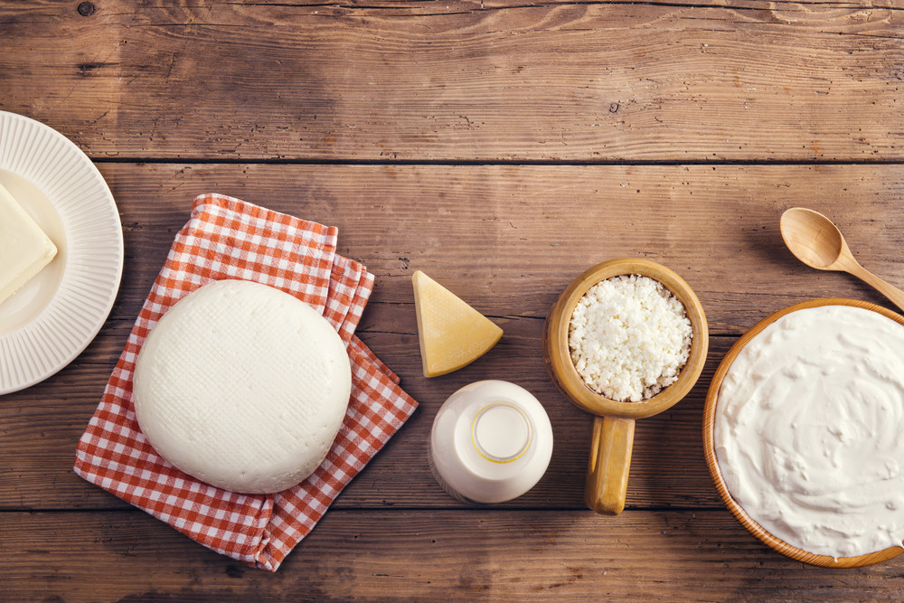 Variety of dairy products laid on a wooden table background