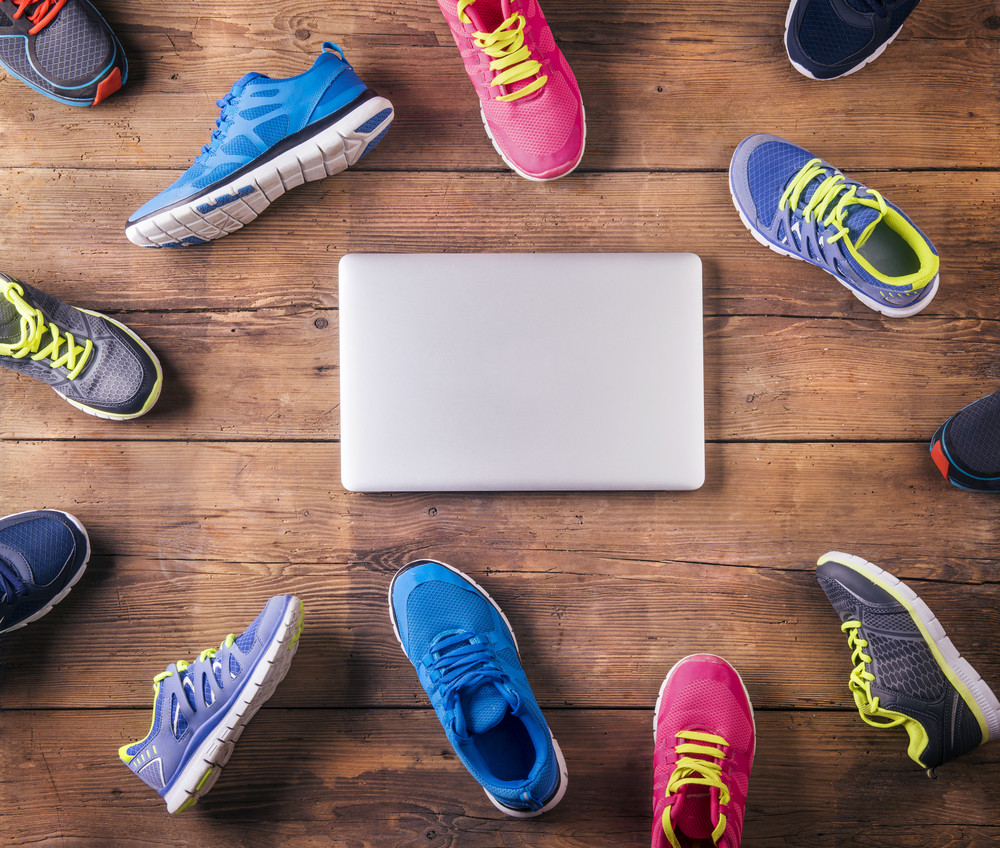 Various running shoes and notebook laid on a wooden floor background