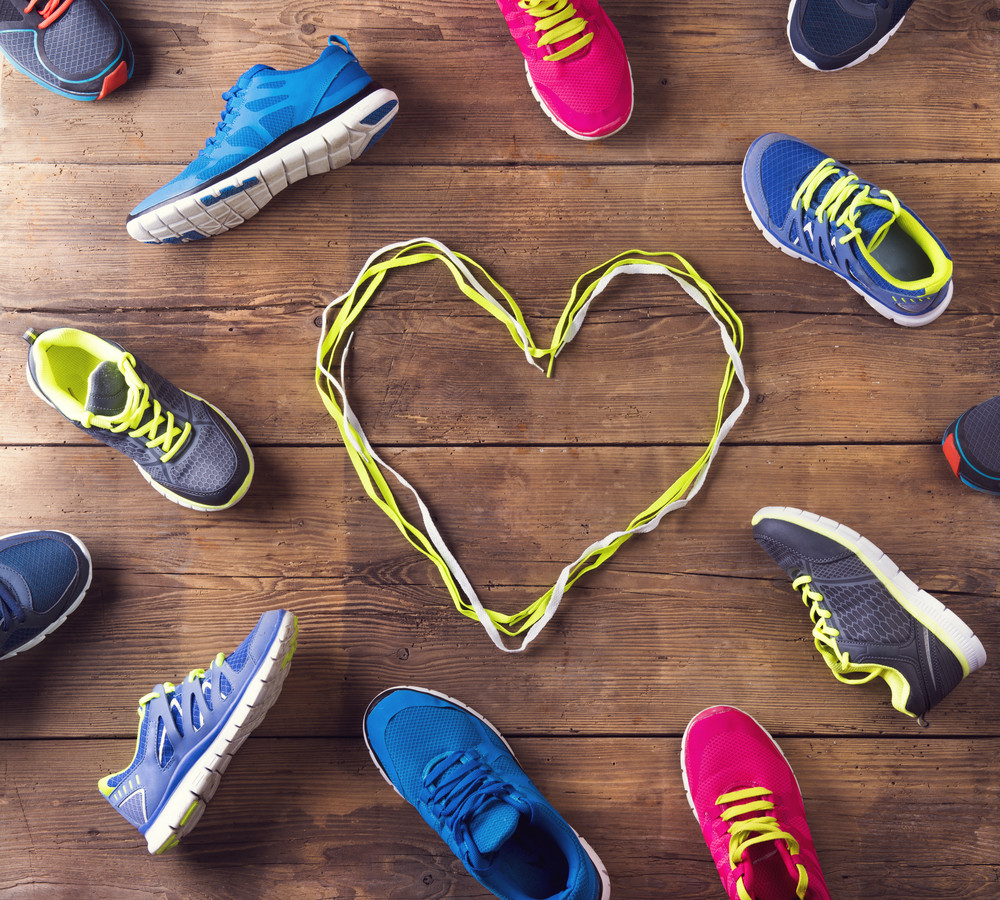 Various running shoes and shoelaces heart on a wooden floor background