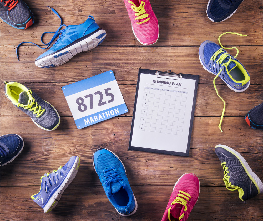 Various running shoes, race number and running plan laid on a wooden floor background