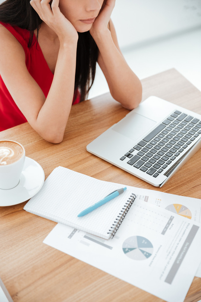 Vertical cropped shot of thoughtful woman in red shirt sitting by the table with laptop and documents in office