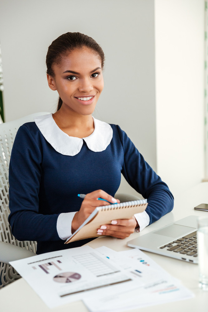 Vertical image of african business woman in dress with notebook and laptop on workplace looking at camera