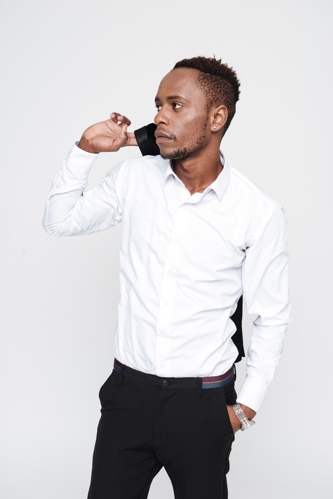 Vertical image of african man in shirt holding arm in pocket and looking away
