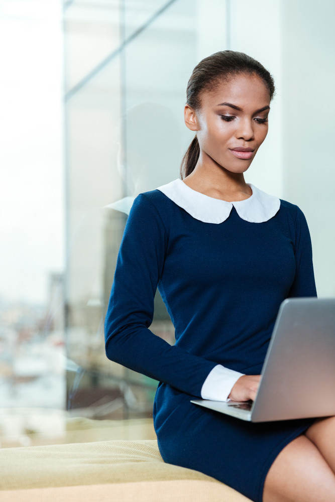 Vertical image of afro business woman in dress sitting near the window with laptop computer