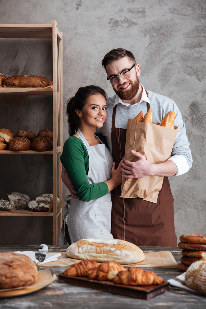 Vertical image of bakers which hugging in bakery and looking at the camera while holding bag with bread
