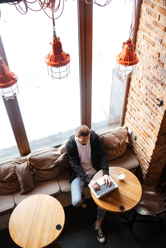 Vertical image of Bearded hipster sitting by the table and using laptop computer in cafe. Top view