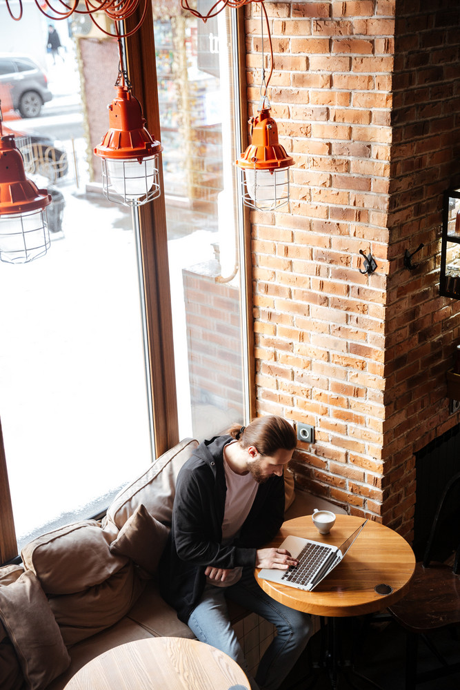Vertical image of Bearded man sitting by the table and using laptop computer in cafe. Top view