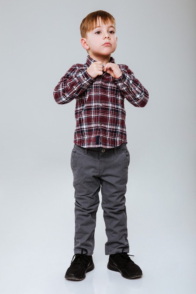 Vertical image of cool young boy buttoning of his shirt. Full length. Isolated gray background
