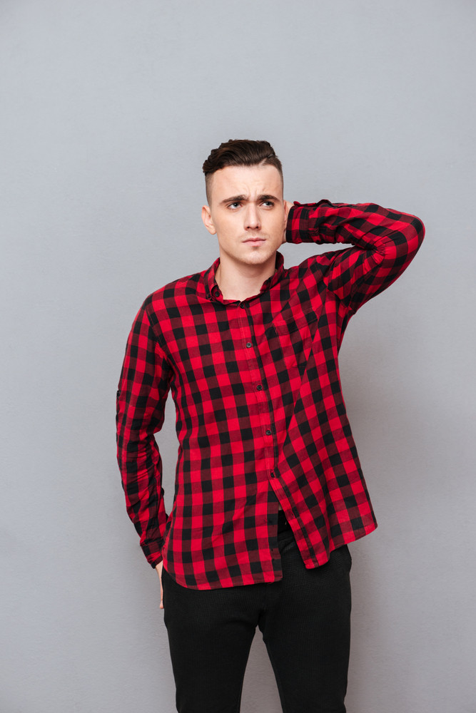 Vertical image of displeased young man in shirt and black jeans. Isolated gray background