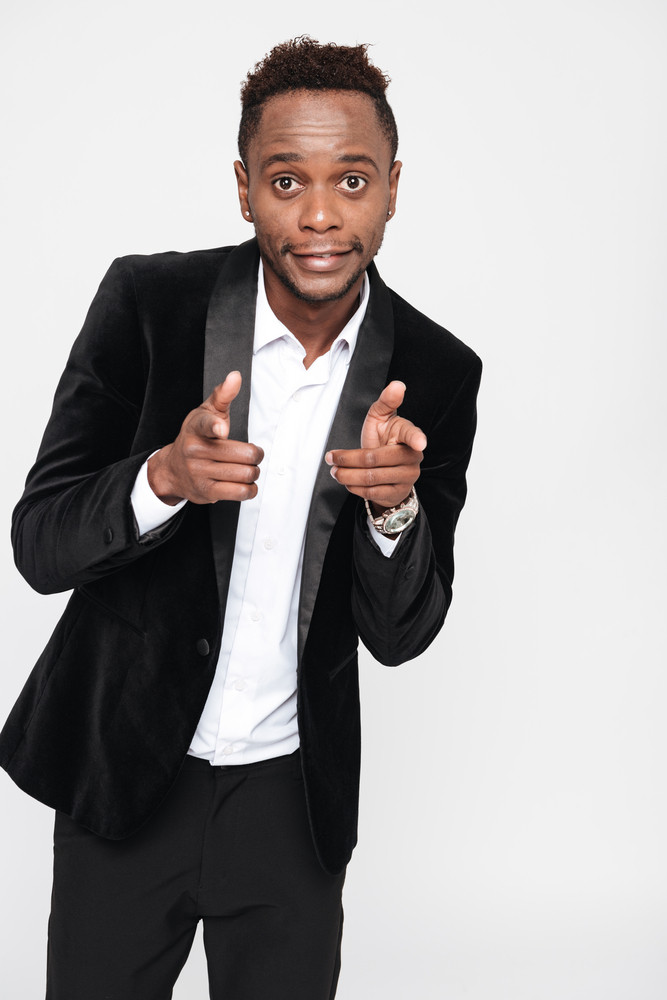 Vertical image of funny african man in suit pointing at camera. Isolated white background