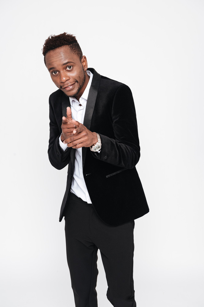 Vertical image of happy african man in suit pointing at camera. Isolated white background