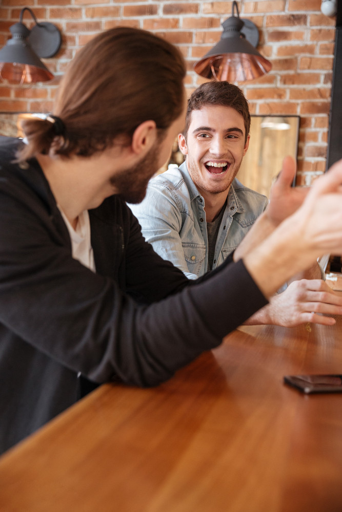Vertical image of happy friends sitting on bar and speaking
