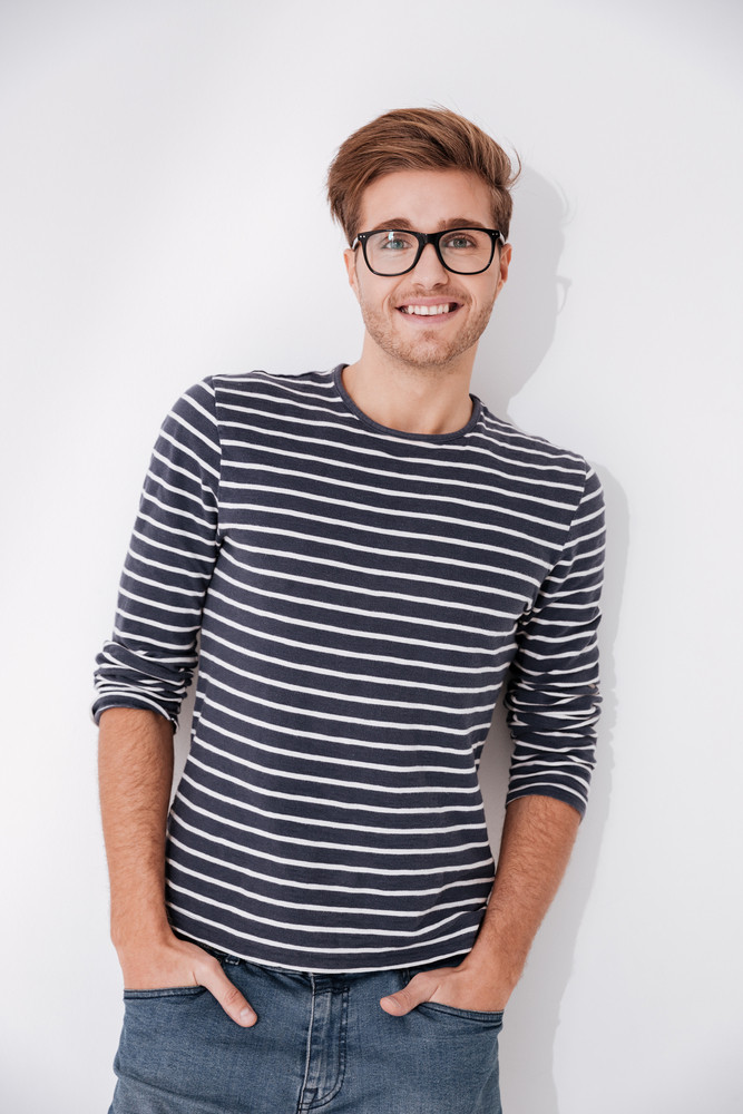 Vertical image of man in striped sweater and glasses posing with arms in pockets and looking at camera. Isolate gray background