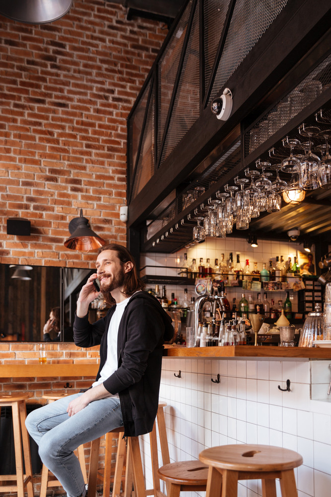 Vertical image of man sitting on bar and talking on phone
