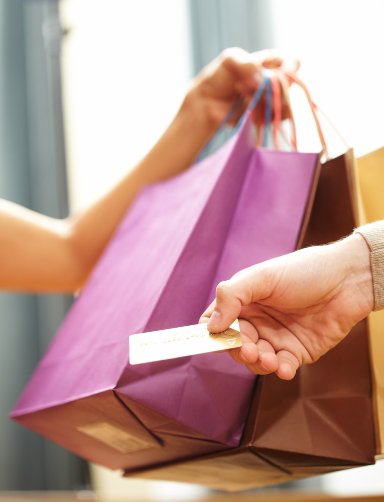 Vertical image of man's hand passing over credit card to shop assistant after shopping