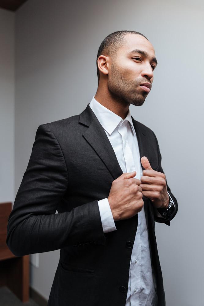 Vertical image of Serious African man preparing in hotel room and looking away