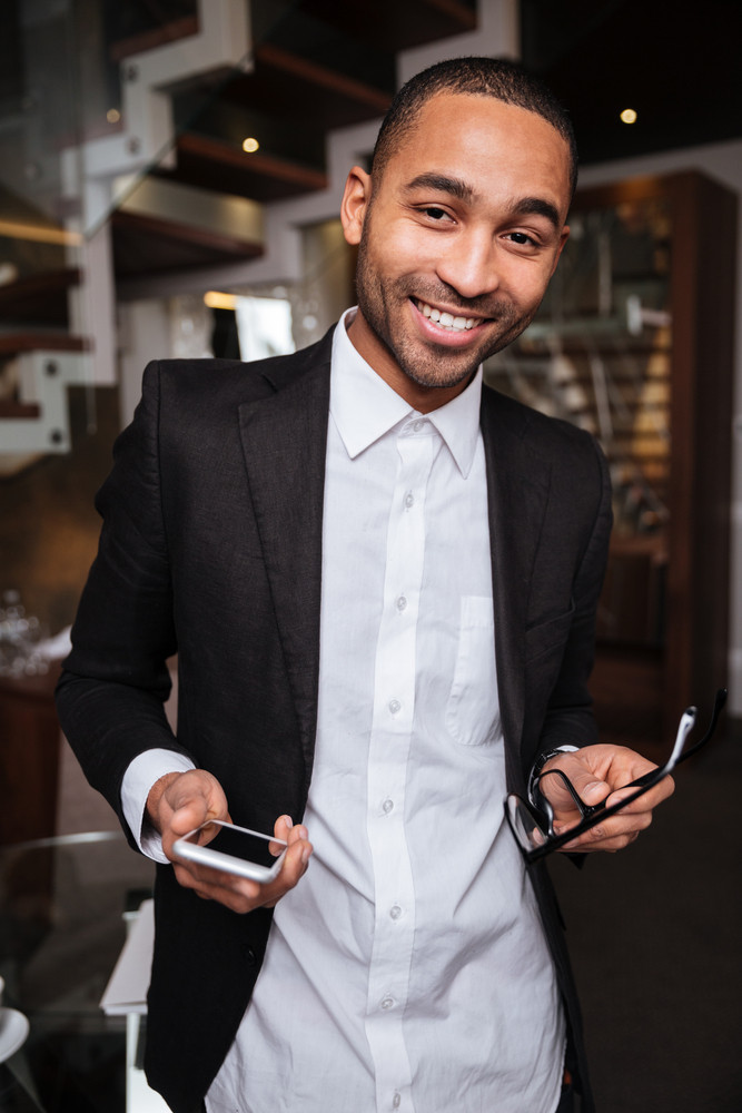 Vertical image of smiling african man in suit holding phone and eyeglases in hotel
