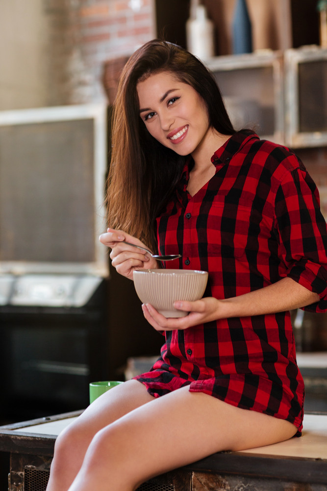 Vertical image of smiling woman in red shirt with naked legs sitting on the table and eating. Side view