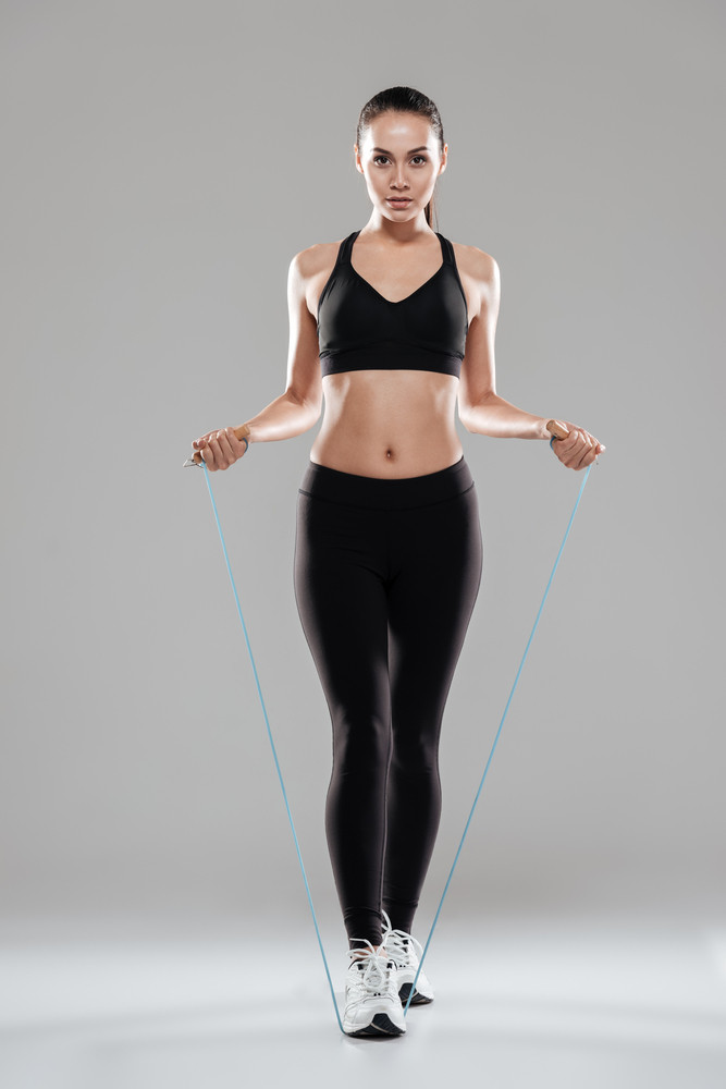 Vertical image of Sporting woman jumping with skipping rope in studio. Full length. Isolated gray background