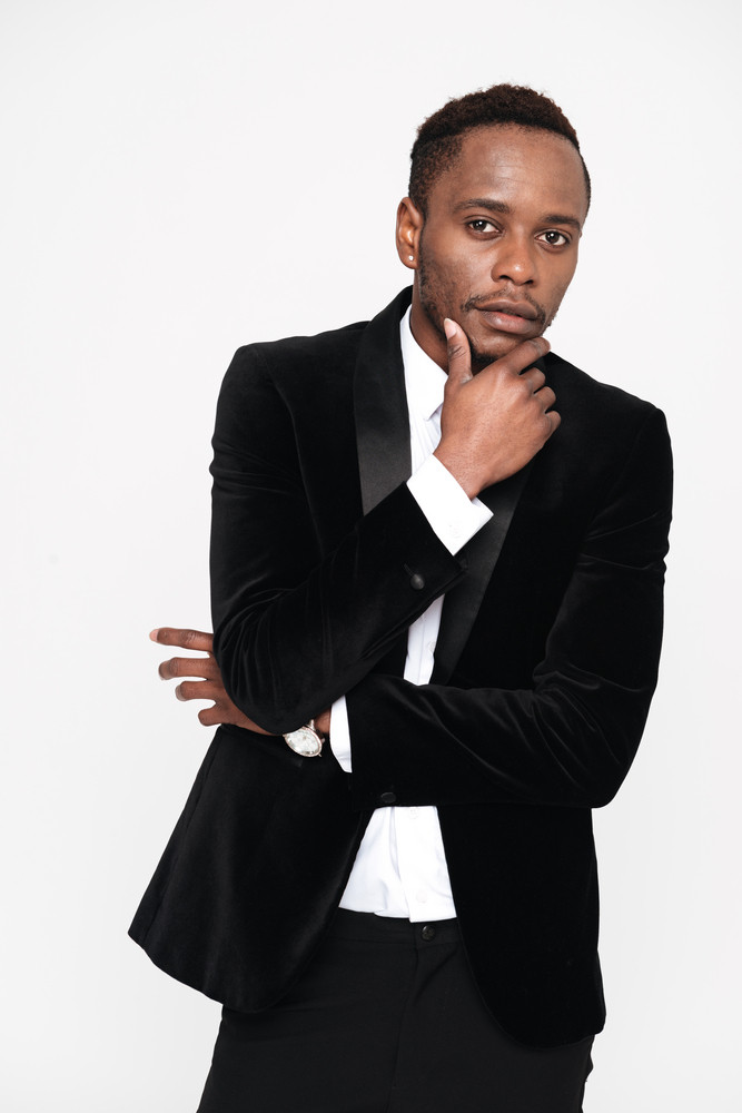 Vertical image of thoughtful african man in suit looking at camera and holding hand near the face. Isolated white background