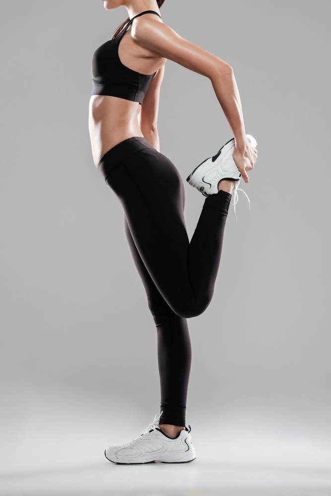 Vertical image of warming up sporting woman in studio. Side view Isolated gray background