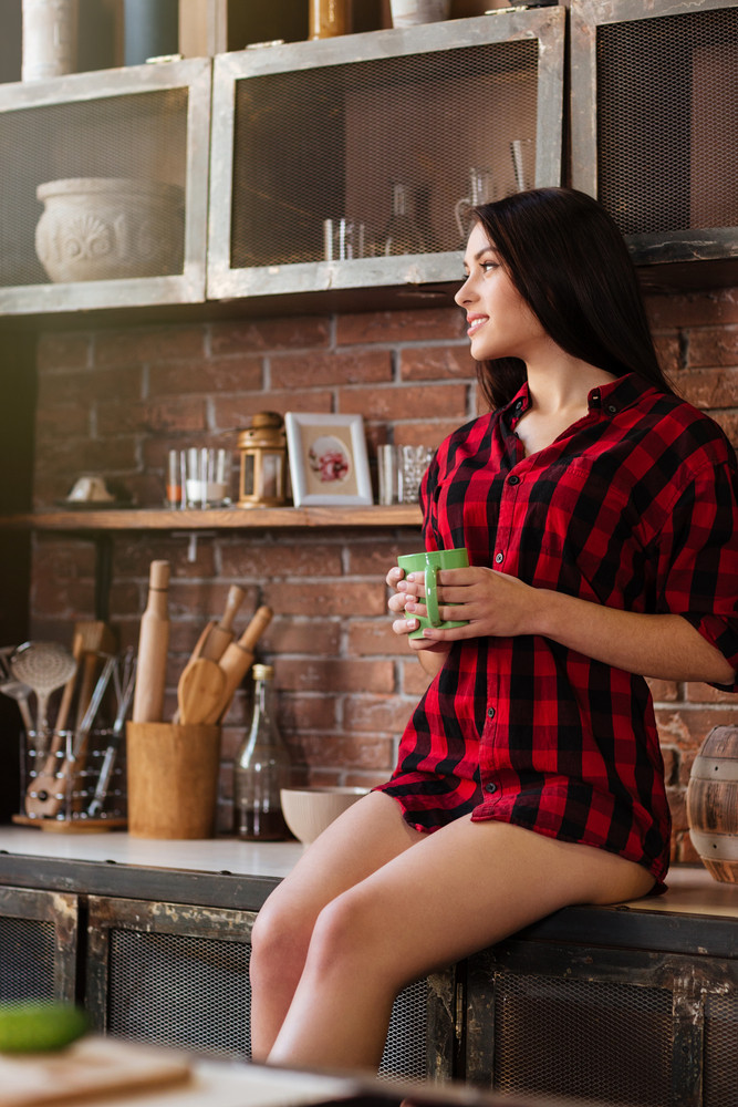 Vertical image of woman in red shirt with naked legs holding cup of tie and looking aside in kitchen. Side view