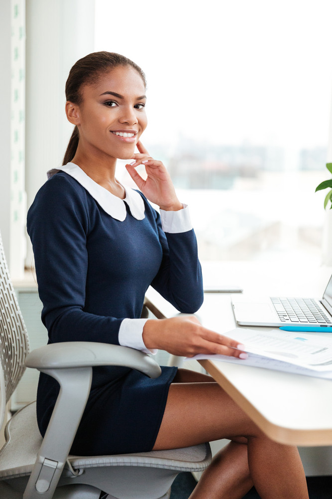 Vertical image of young african business woman in dress sitting on armchair near the window in office and looking at camera