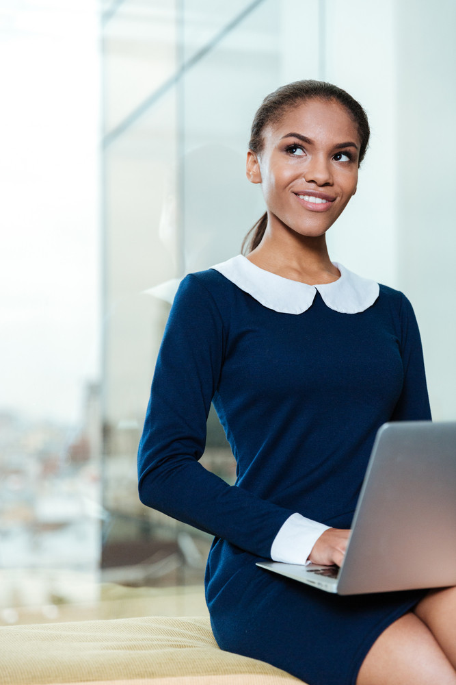 Vertical image of young afro business woman in dress sitting near the window with laptop and looking away in office