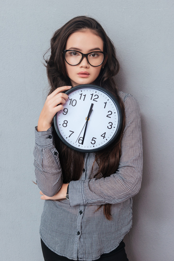 Vertical image of young cute asian woman in glasses holding clock and  looking at camera.