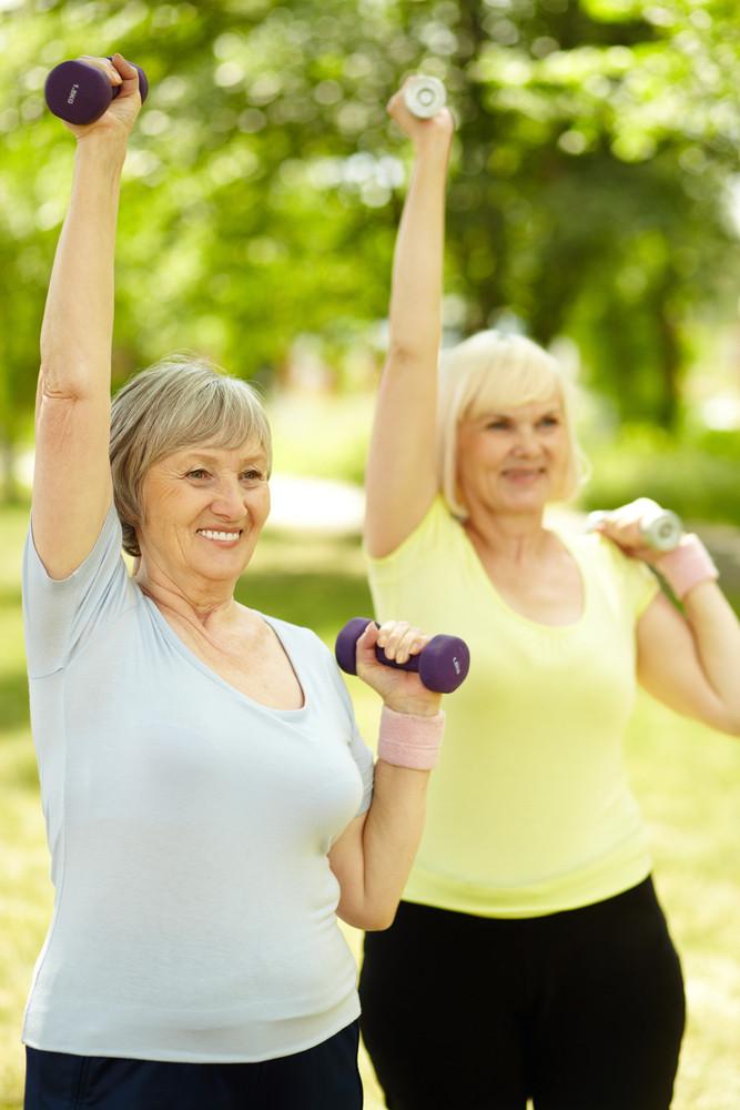 Vertical shot of elderly women doing exercises with dumbbells