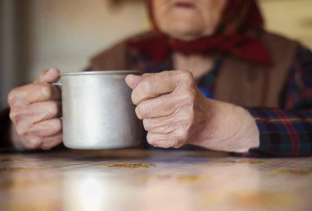 Very old woman in head scarf is drinking tea in her old country style kitchen