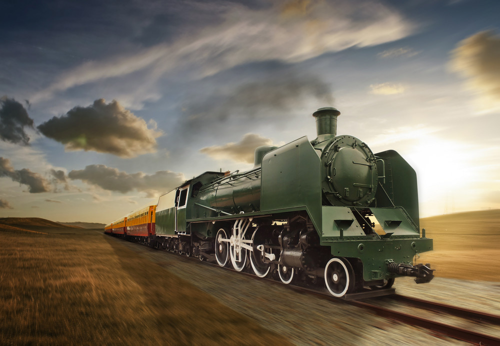 vintage green and yellow steam powered railway train moving